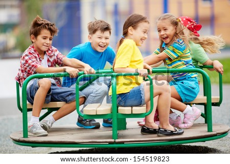 Image of joyful friends having fun on carousel outdoors  Royalty-Free Stock Photo #154519823