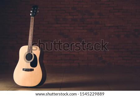 Modern acoustic guitar against dark wall