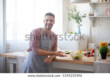 Husband welcoming. Husband wearing apron welcoming his wife in the kitchen after cooking salad #1545235496