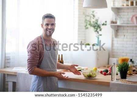Satisfied after cooking. Smiling young businessman feeling satisfied after cooking at home #1545235499