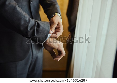 Businessman wears a jacket,male hands closeup,groom getting ready in the morning before wedding ceremony #1545316289