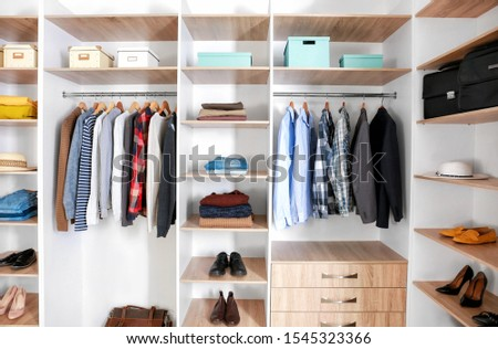 Big wardrobe with clothes in dressing room #1545323366