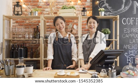 Portrait of cheerful asian female barista laughing during working break together with positive smile. Partnership of youg women in common business cafeteria. two girl staff face camera in coffee shop #1545352385