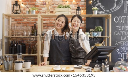 Couple of barista working in coffee shop. two attractive young women coffehouse staffs standing together behind bar counter face camera and smiling. group of cute female waitresses in apron joyful. #1545353195