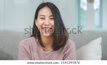 Teenager Asian woman feeling happy smiling and looking to camera while relax in living room at home.  #1545395876