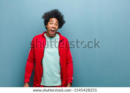young black sports man looking very shocked or surprised, staring with open mouth saying wow against grunge wall #1545428255