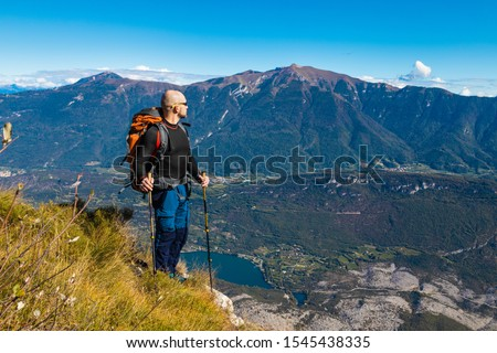 A man traveler with a backpack stands on a hill of beautiful alpine landscape #1545438335