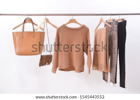 brown wool sweater with scarf, and brown, and snake pattern handbag with pants and black pants on hanger  #1545443552