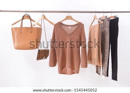 brown wool sweater with scarf, and brown, and snake pattern handbag with pants and black pants on hanger  #1545445052