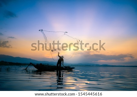 Lifestyle of Asian fisherman on wooden boat for catching freshwater fish in reservoir in the early morning before sunrise Royalty-Free Stock Photo #1545445616