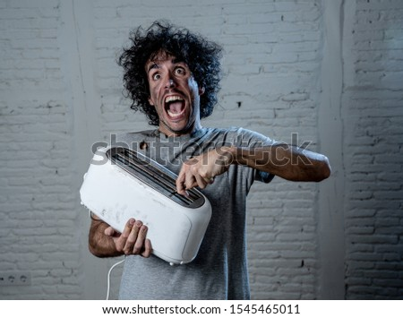 Domestic accidents and electricity danger. Young man electrocuted trying to get toast out of toaster with knife. Husband screaming as getting an electric shock with dirty burnt funny face expression. #1545465011