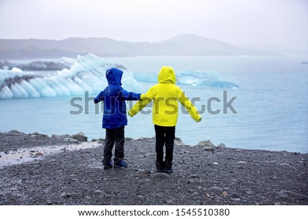 Child, taking picture at early evening on a rainy day at picturesque iceberg lagoon Jokursarlon in Iceland