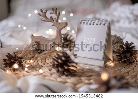 New Year 2020 grey calendar with lights on rustic server with cones and wooden Christmas tree toys #1545513482