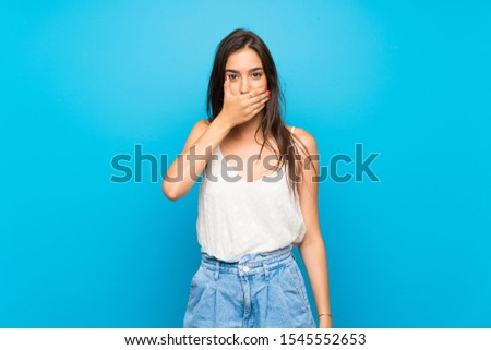 Young woman over isolated blue background covering mouth with hands #1545552653