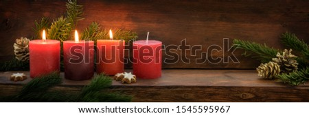 Third Advent, three of four red candles are lit with a flame, fir branches and Christmas decoration on dark rustic wood, wide panoramic format with copy space, selected focus #1545595967