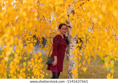 Yakut Asian young happy girl dress with handbag with glasses and with ornaments hugging birch with yellow leaves in autumn. #1545637661