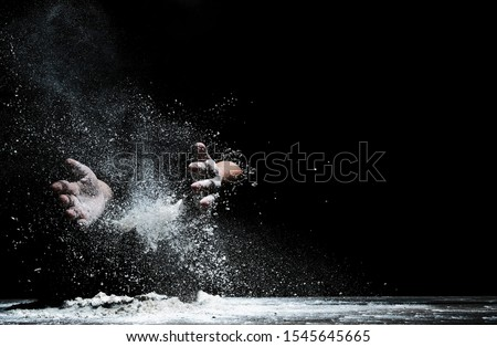 Chef hand clap and white flour on black background #1545645665