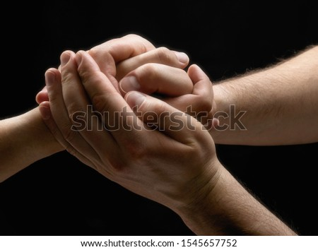 Male and female hands connect with each other. On black background. Image. #1545657752