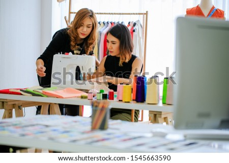 Two Young Asian designer woman working with sewing new dress at workplace,small business startup, Business owner entrepreneur, Dressmaker,fashion designer,modern freelance job lifestyle concept #1545663590