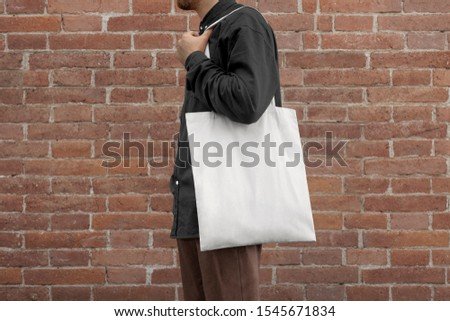 Urban mockup of tote bag. Men holding black cotton tote bag on a wall background. Template can be used for you design  #1545671834