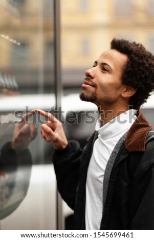 African man buys drink or sweets at vending machine outside. #1545699461