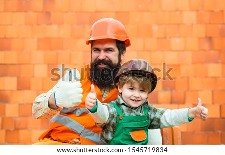 Thumbs up against the background of a brick wall. Construction concept. Happy family together. Happy father and son in safety helmets. #1545719834