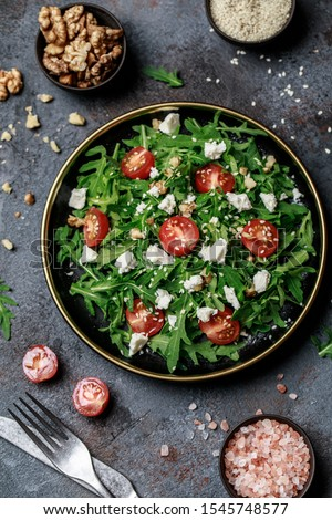 Healthy vegetable salad with fresh arugula, tomato, feta cheese and walnut on dark plate. Diet menu. Top view. Salad with arugula  #1545748577