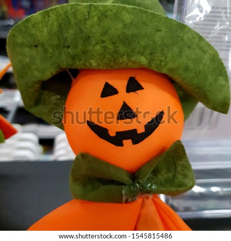 Macro photo Halloween decor pumpkin. Stock photo interior decor pumpkin toy dall