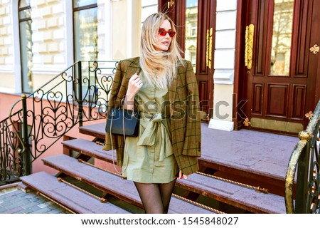 Outdoor fashion portrait of young elegant woman wearing trendy oversized jacket, mini dress and small leather black bag, posing on Paris street , toned warm colors. Royalty-Free Stock Photo #1545848027