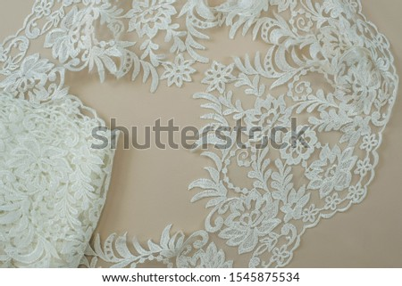 Texture lace fabric. lace on white background studio. thin fabric made of yarn or thread. a background image of ivory-colored lace cloth. White lace on beige background. #1545875534