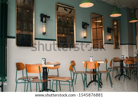 Warsaw, Poland, 28 september 2019.Green and white loft retro cafe interior with small square tables and wooden chairs and mirror. Retro Coffee shop interior. #1545876881
