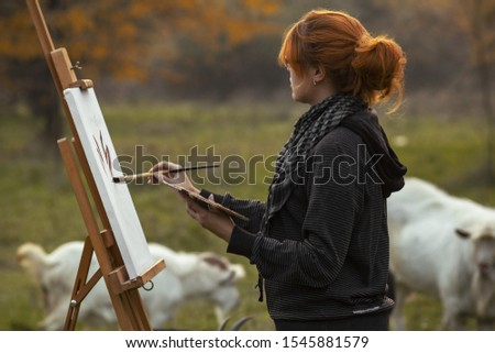 young female painter drawing picture at easel on nature surrounded by grazing goats, the girl engaged in art in rural atmosphere at sunset among farm animals