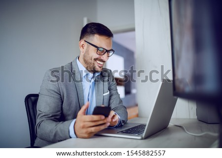 Positive caucasian elegant businessman in suit and with eyeglasses holding smart phone while looking at laptop. Office interior. #1545882557