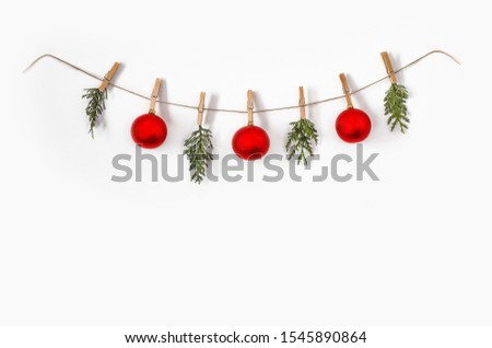 White wall background with christmas composition. Retro rope girland made of three red balls and fir branches. Christmas, cold winter, happy new year. Flat lay photo, top view, copy space.  #1545890864