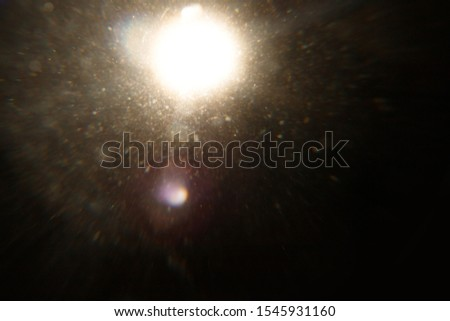 Lens Flare. Light over black background. Easy to add overlay or screen filter over photos. Abstract sun burst with digital lens flare background. Gleams rounded and hexagonal shapes, rainbow halo. #1545931160