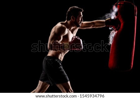 Boxer punching a bag with dust particles coming out over a black background Royalty-Free Stock Photo #1545934796