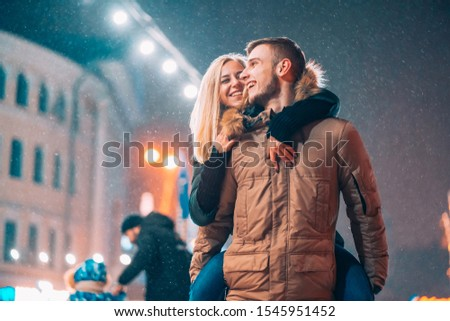 Cheerful and playful couple in warm winter outfits are fooling around #1545951452