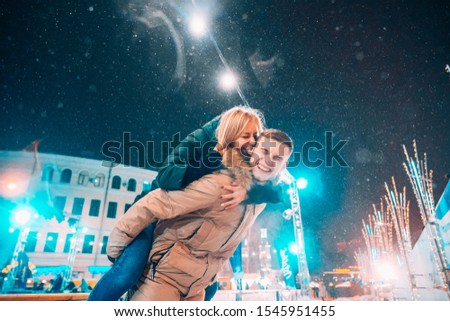 Cheerful and playful couple in warm winter outfits are fooling around #1545951455