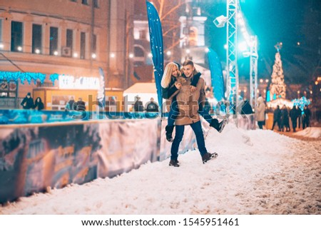 Cheerful and playful couple in warm winter outfits are fooling around #1545951461