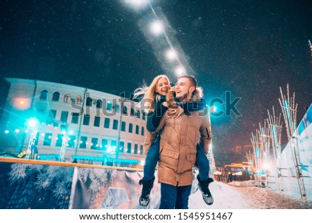 Cheerful and playful couple in warm winter outfits are fooling around #1545951467