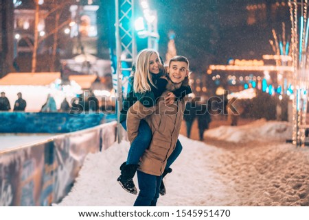 Cheerful and playful couple in warm winter outfits are fooling around #1545951470