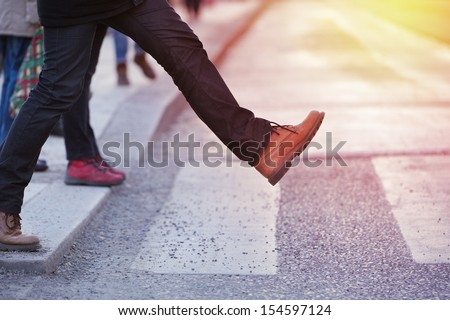 Man taking the step (onto zebra crossing) #154597124