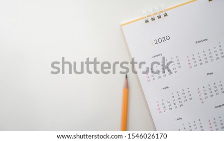 close up top view on white calendar 2020 with yellow pencil and month schedule to make appointment meeting or manage timetable each day lay on brown wood table background for planning work and life