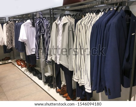 Collection of long sleeve blue shirts,suit , business clothes ,and different leather shoes, handbag on shop     #1546094180