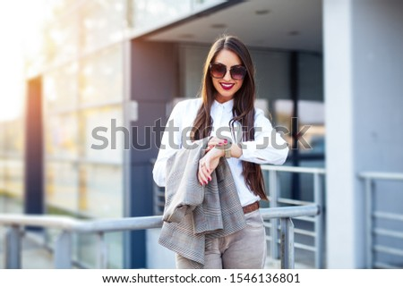 Business woman looking at watch at office building #1546136801