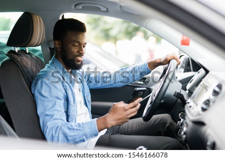 In car view of young male African American holding his phone #1546166078