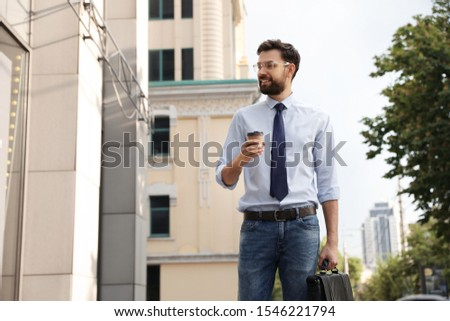 Handsome businessman in stylish outfit on city street #1546221794