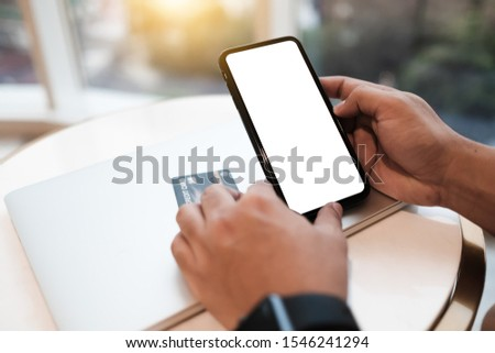 Close up of man using blank cell phone and credit card sending massages shopping online on the coffee shop.