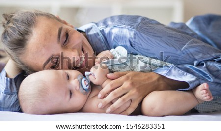 Safe in mommy's arms. Mother and her baby boy at home. #1546283351