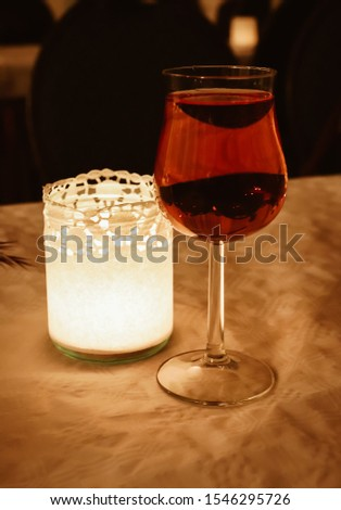 Glass of red wine next to a candle #1546295726